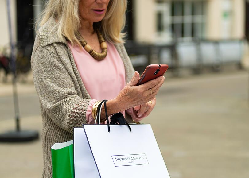 lady carrying shopping bags looking at her phone